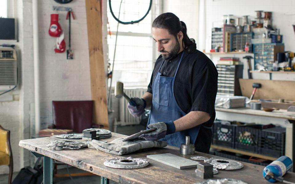 Маджян начал компанию Sartonk вместе со своей женой Асмик Татиоссян. Здесь он использует молоток, чтобы придать форму медальону, который еще свежим пришел из формы.