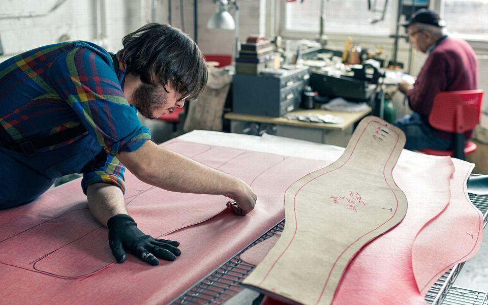 Джордж Гарсия обрезает материал, который будет использован для создания ремня. Саакян, который на самом деле официально в отставке, проводит почти все свое время в мастерской, наблюдая за производством.