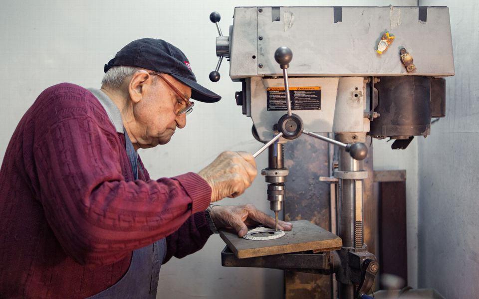 Саакян работает со сверлом, чтобы проделать отверстия на медальоне, который будет потом привинчен к кожаному поясу.
