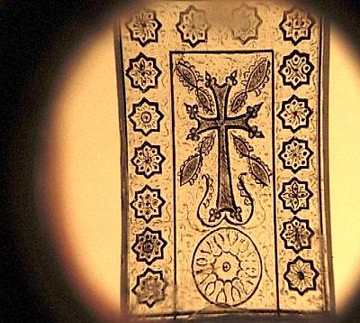 Другой хачкар, выгравированный на янтарной поверхности, сопровождаемый армянскими народными орнаментами.