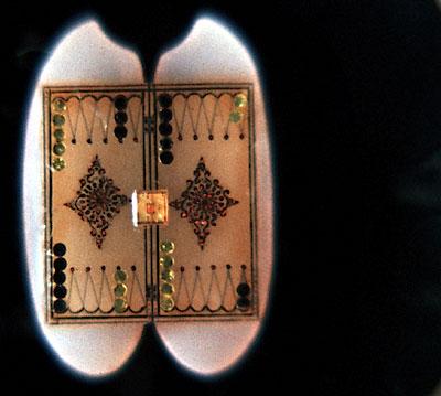 Самая маленькая доска для игры в нарды, сооруженная на гранях риса. Доска сделана из обсидиана и золота.