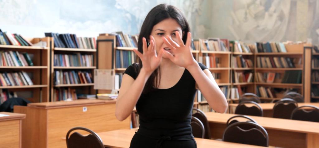 Кадр из видео с участием слышащей девушки, которая на армянском жестовом языке читает стихотворение современной армянской поэтессы Кристине Бежанян.